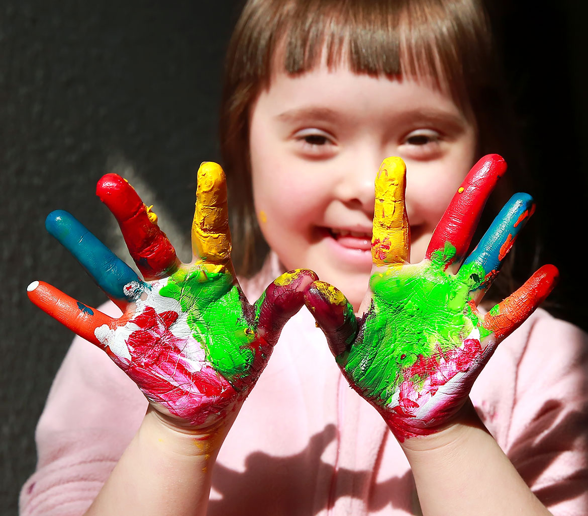 young girl smiling with both hands in multicolour paint